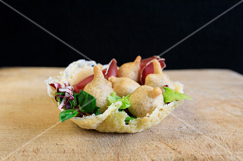 Sciatt (croquettes with cheese) and bresaola in a Parmesan bowl (Veltlin, Lombardy, Italy)