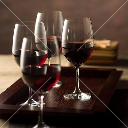 Vier Rotweingläser auf Holztablett
