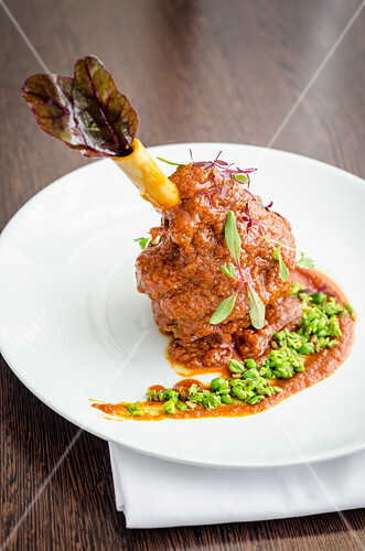 Slow cooked lamb shank in a rich tomato, yogurt, turmeric and peas sauce on a white plate and wooden background