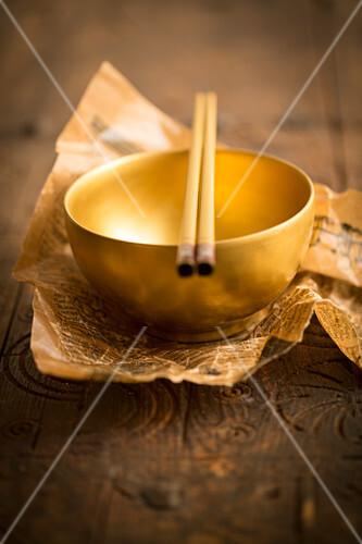 A golden bowl with chopsticks