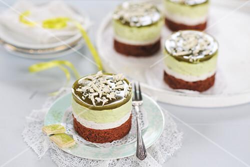 Matcha cream tarts with dark chocolate bases, almond and tonka bean cream, white chocolate and matcha cream, matcha jelly, and grated white chocolate (vegan)