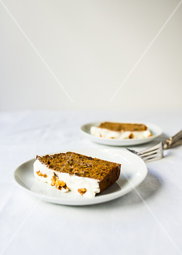 Slices of banana bread with walnuts and icing, on plates