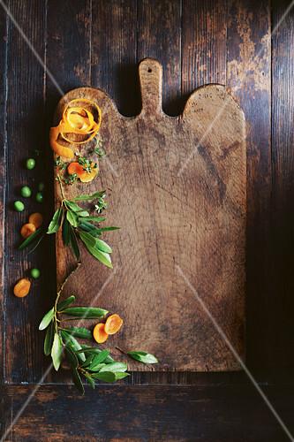 Olivenblätter, Orangenschale und getrocknete Aprikosen auf Holzschneidebrett
