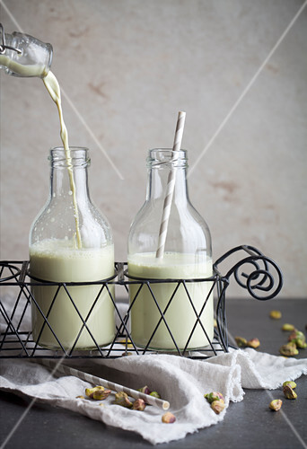Homemade pistachio milk with straws in bottles