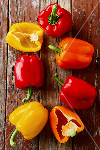 Red, yellow and orange peppers on a wooden background