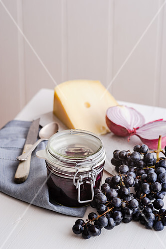 A jar of red grape chutney surrounded by cheese, onions and grapes