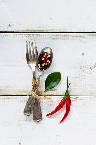 Spices, red hot chili peppers with vintage fork and spoon on white wooden background