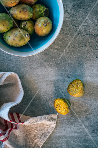 Fresh prickly pears in a bowl and on a grey stone background (top view)