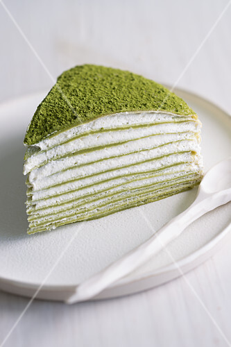 A piece of Mille Crepes cake (pancake cake) with matcha and cream filling