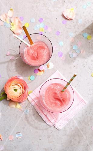 Zwei Gläser Frosé, Ranunkelblüte und Konfetti auf Betonuntergrund