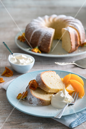 Lemon wreath cake served with cream and apricot compote (Italy)