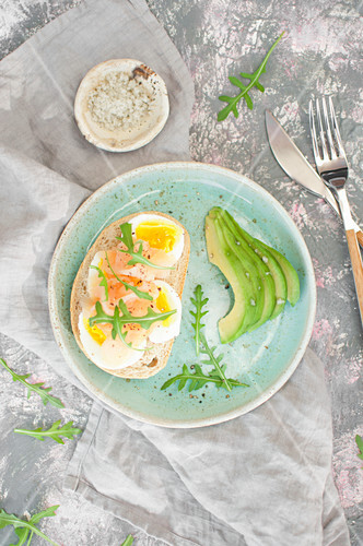 Healthy breakfast. Toast with egg, smoked salmon and arugula