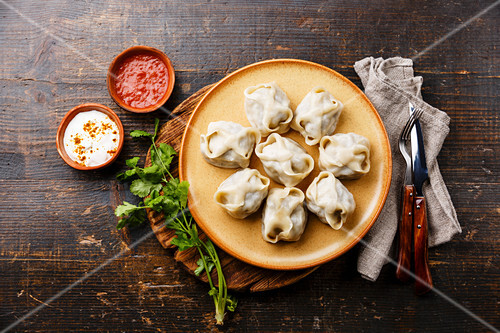 Traditional steamed dumplings Manty with Yogurt and Tomato sauce