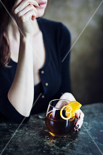 Young woman sitting at bar drinking a alcoholic drink
