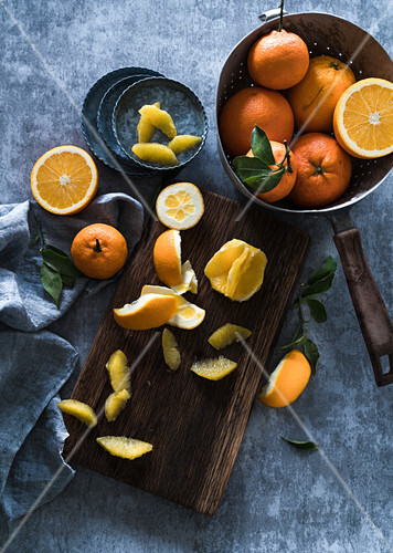 Fresh oranges in a metal colander, with orange fillets on a wooden board and small plates