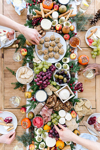 A savoury selection board for friends, with cheese, grapes, olives, breads, ham, eggs and fruit