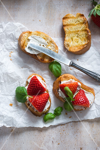 Toasted baguette slices with almond cream cheese, strawberries and basil (vegan)
