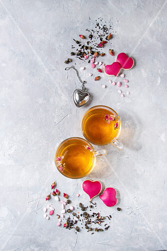 Love Valentines day greeting card with two glasses of hot tea, rose buds, heart shape homemade cookies as gift, pink sugar, tea strainer over gray texture background