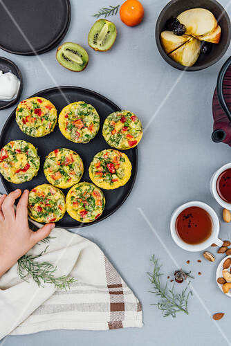 A kid grabbing a vegetarian breakfast omelet muffins from a black plate photographed from top view