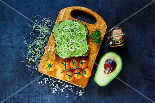 Fresh vegetarian sandwich with whole grain bread, alfalfa and guacamole on rustic wooden cutting board over dark vintage background