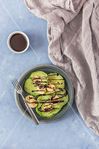 Green pancakes with banana and chocolate sauce