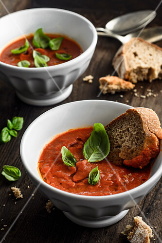 Roasted tomatoes cream soup with basil and slice of bread