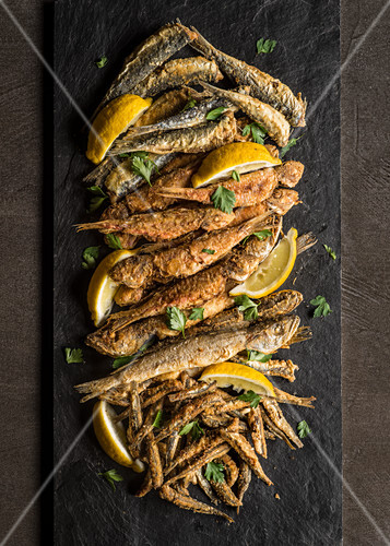 Assortment of fried fish with lemon wedges and parsley on slate plank and dark background