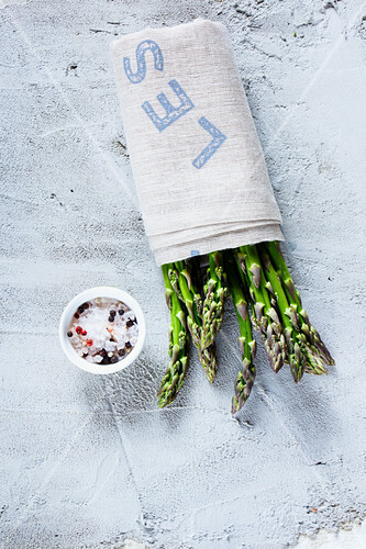 Fresh green asparagus wrapped in a cloth, with a bowl of spices
