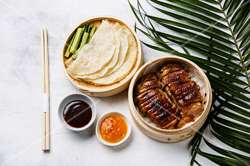 Sliced Peking Duck in bamboo steamer served with fresh cucumber, roasted wheaten chinese pancakes and sauce Hoysin on white wooden background