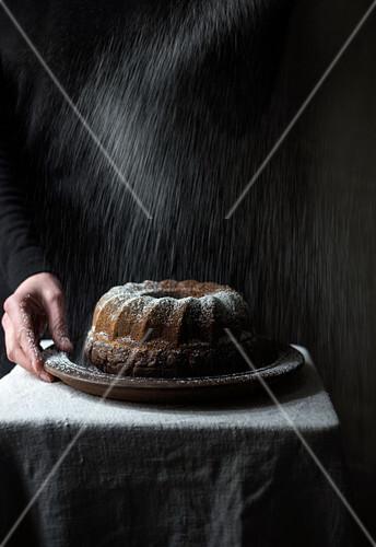 Frau bestäubt veganen Gugelhupf mit Puderzucker