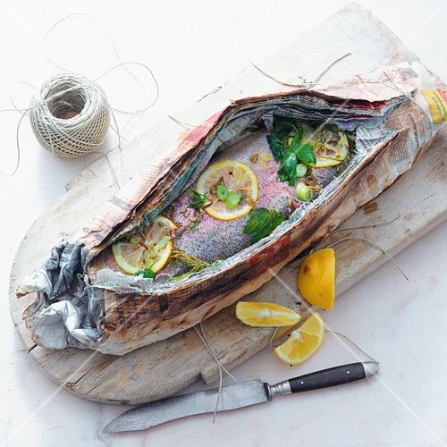 Grilled trout wrapped in newspaper
