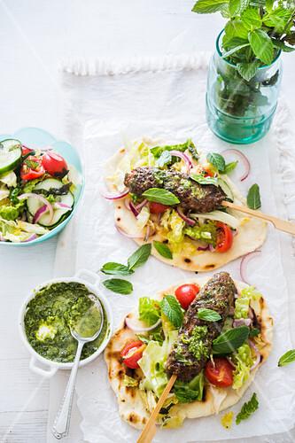 Two pita breads with kofta, mint sauce and fresh salad
