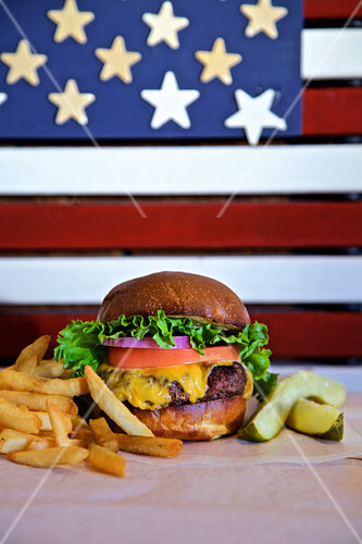 Cheese burger with lettuce tomato, onion, pickle and french fries with american flag