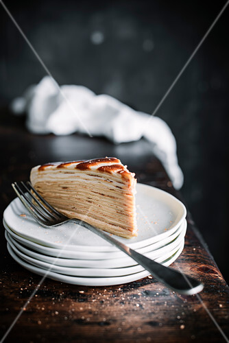 A slice of pancake cake with caramel on a stack of plates