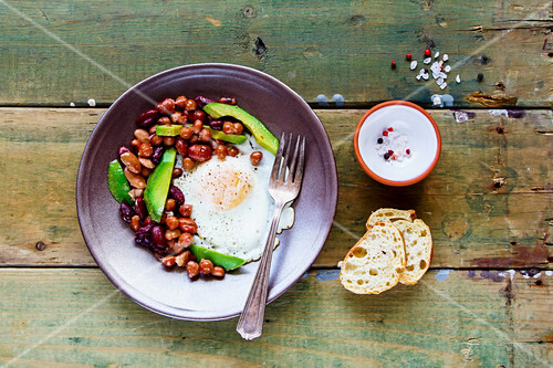 An English breakfast with baked beans, fried eggs and avocado