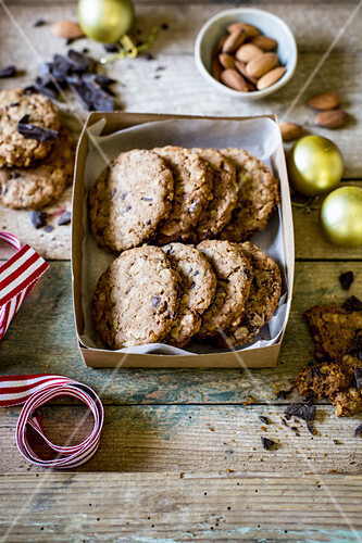 Festive chocolate chip, almond and oat cookies as a gift for christmas on rustic wooden surface