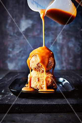 Vanilla ice cream coated in biscuit crumbs, drizzled with caramel sauce