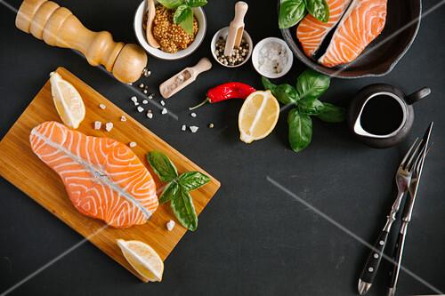 Stillleben mit Lachs, Gewürzen, Basilikum und Zitrone