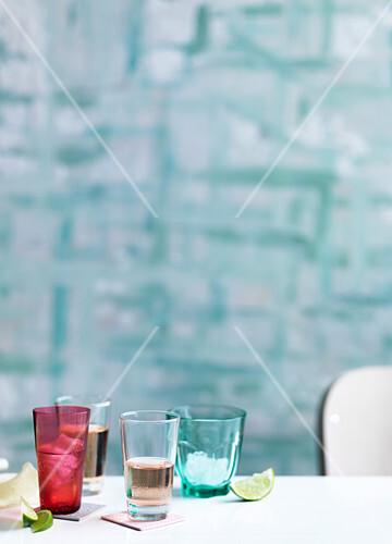 Coloured glasses, pink, lime wedges, blue background