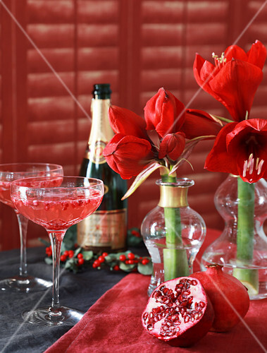 Champagne saucers, pomegranate and amaryllis on set table