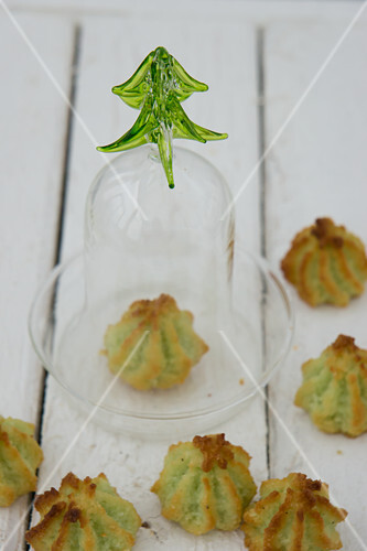 Pistachio and coconut macaroons with one under a glass cloche