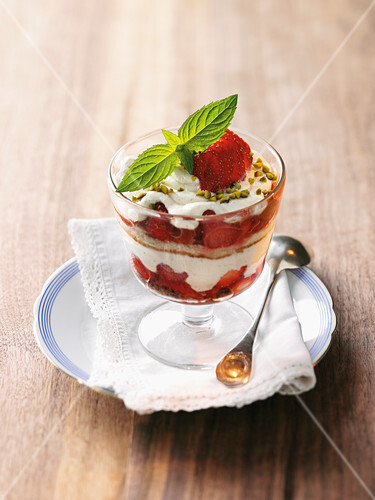 Strawberry and rhubarb sponge cake with pistachio nuts in a glass