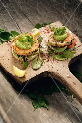 Open fish burgers with rice crackers and avocado cream
