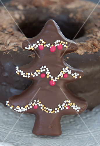 A chocolate-glazed gingerbread Christmas tree with sprinkles