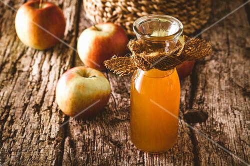 Apfelessig in Glaskaraffe auf Holzuntergrund