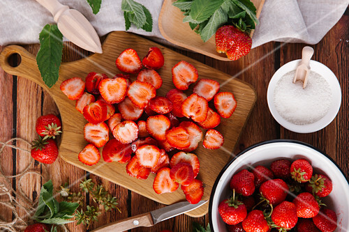 Fresh strawberries, cleaned and sliced, and a bowl of sugar