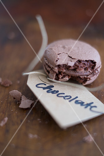 A chocolate macaron with a paper tag
