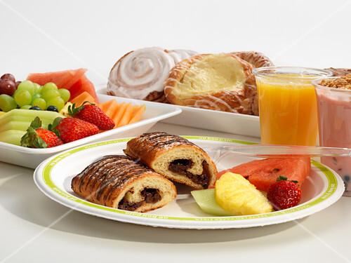 Breakfast with pastries, fruit, yogurt and orange juice