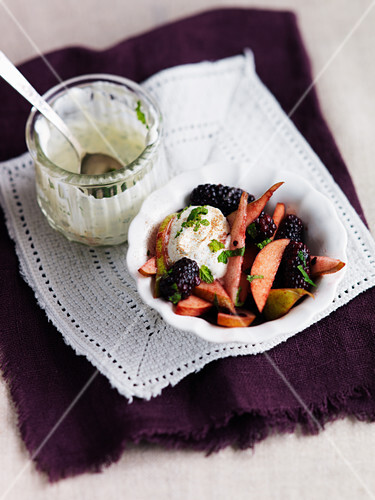 Fruit salad with cream, blackberries, pears and mint