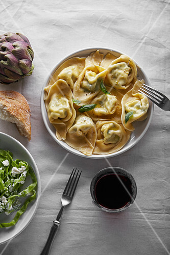 Overhead image of traditional italian ravioli with ricotta cheese and spinach tagliatelle served with a glass of wine